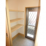 キッチン横には土間付きの勝手口。デッドスペースに棚を設置し、外で使う用具を収納できるようにしました。
